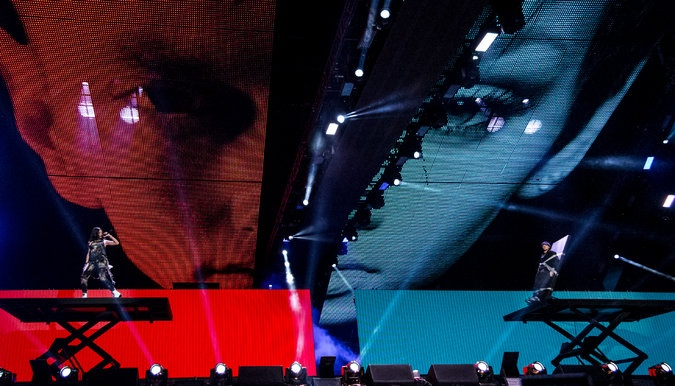 The Monster Tour, August 2014. Performers on hydraulic lifts in front of tracking video walls. Photo: New York Times.